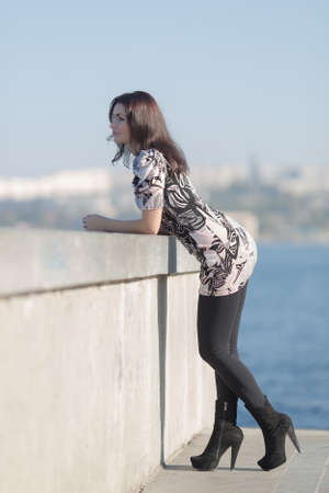 eastern european ethnicity: Attractive woman on seafront stands by the concrete wall and looks into the distance