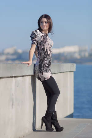 Attractive woman on seafront stands by the concrete wall and looks away photo