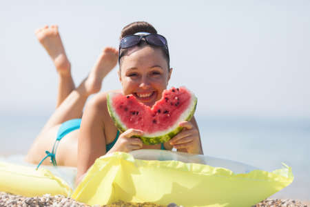 Girl at the sea. Young woman eats watermelon on seashore photo