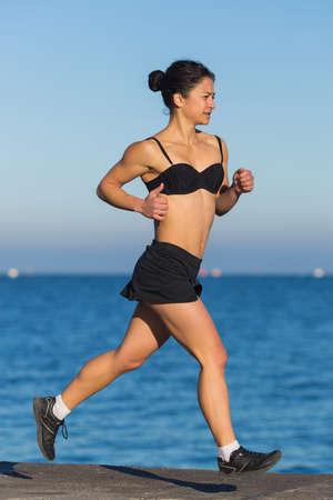 Jogging. Asian girl running along the beach photo