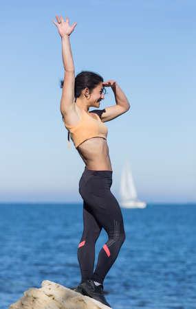 observes: Brunette on seashore. Young woman in sportswear observes yacht in sea