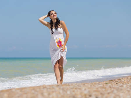 expectant mother: Pregnant woman in white dress at the sea. Expectant mother on the beach