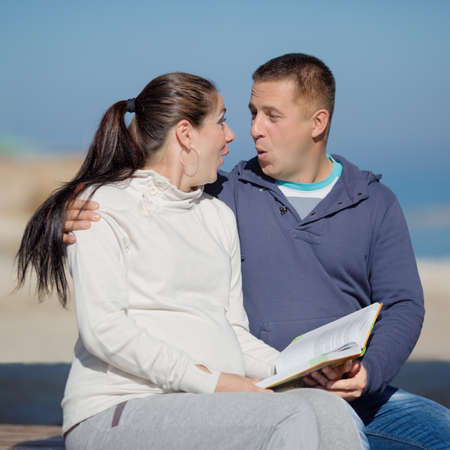 in the open air: Attractive couple on seashore. Young man and woman reading book sitting on open air Stock Photo