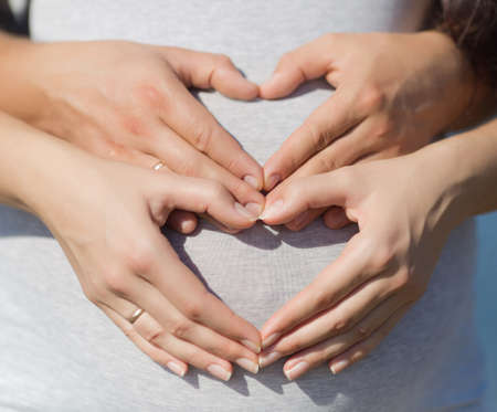 expectant mother: Four hands on belly of expectant mother. Couple posing a hearts with their fingers on belly of expectant mother