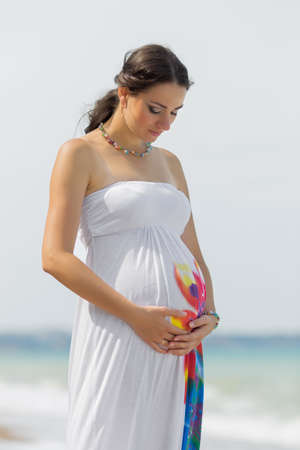 expectant mother: Expectant mother on the beach. Pregnant woman in white dress at the sea