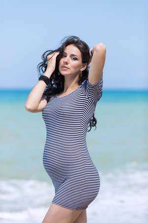 expectant arms: Expectant mother on the beach. Pregnant woman in striped dress at the sea