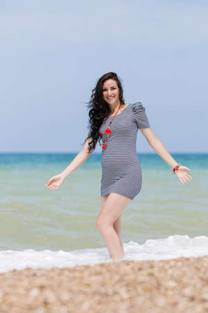 expectant mother: Expectant mother on the beach. Pregnant woman in striped dress playing at the sea