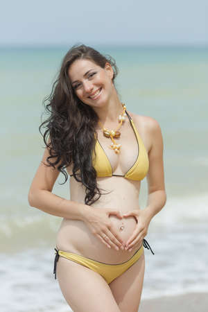 expectant mother: Expectant mother in yellow bikini at the sea.