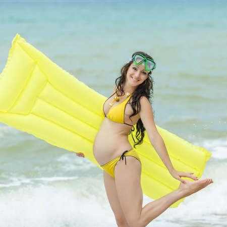 Expectant mother with pool raft and diving mask looking at camera.