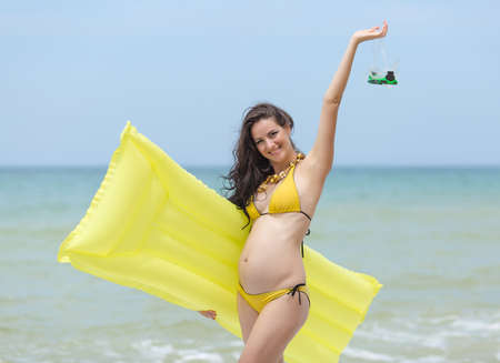 expectant mother: Expectant mother with pool raft and diving mask posing at the sea. Pregnant woman in yellow bikini on the beach