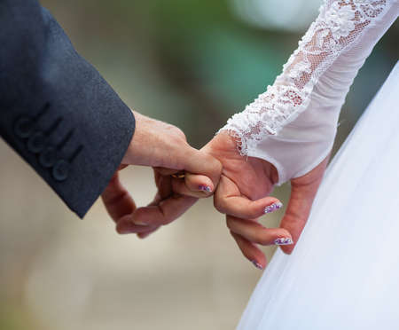 newly wedded couple: Man and woman making a pinkie promise Stock Photo