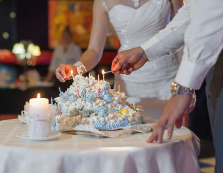 newly wedded couple: Bride and groom are burning candles on their wedding cake