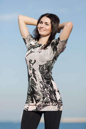in the open air: Girl on seafront. Cute young woman with arms raised posing on open air