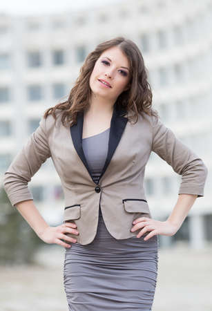 hands on waist: Attractive business woman in town. Urban young woman posing with hands on her waist
