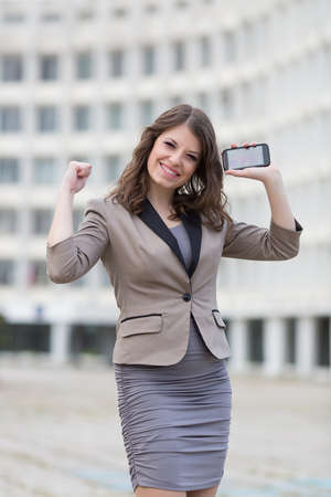 eastern european ethnicity: Attractive business woman holds smartphone. Urban young woman showing positive emotion with hands raised