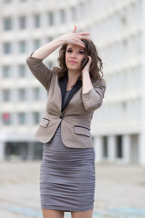 russian ethnicity caucasian: Attractive business woman in town. Urban young woman talking by phone adjusting her hairstyle