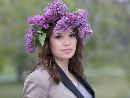 eastern european ethnicity: Portrait of young woman in lilac wreath outdoors. Girl with lilac flowers on head looking at camera