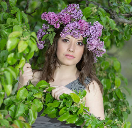 pear tree: Portrait of young woman in lilac wreath. Girl with lilac flowers on head surrounded by leaves of pear tree Stock Photo