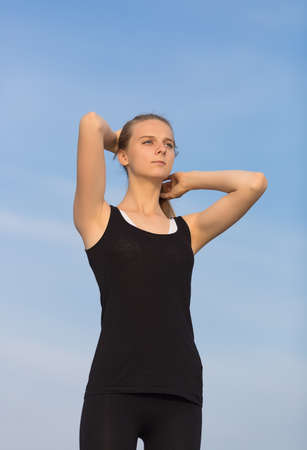 non moving activity: Young woman in black sportswear stands with arms raised. Slim girl corrects own hairstyle looking away