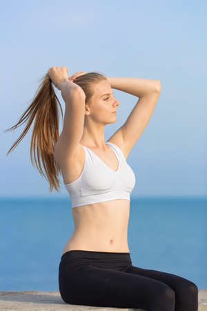 Young woman in sportswear at the sea. Slim girl sitting on concrete pier corrects own ponytail looking away
