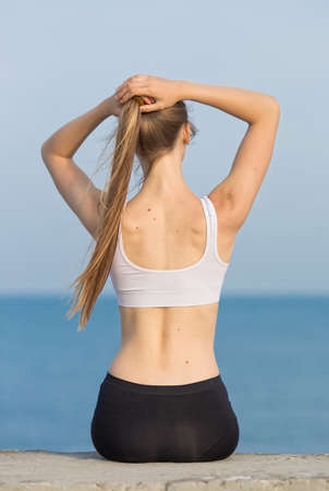 girl in sportswear: Young woman in sportswear at the sea. Slim girl sitting on concrete pier corrects own ponytail, rear view