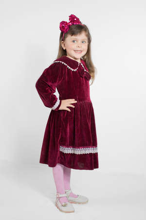 velvet dress: Portrait of preschooler girl in velvet dress. Charming child posing on white background indoors. Studio shot Stock Photo