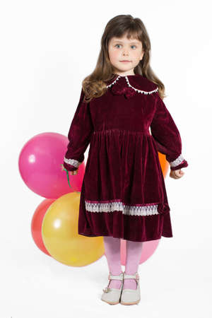 velvet dress: Portrait of preschooler girl in velvet dress. Charming child with air baloons posing on white background indoors. Studio shot Stock Photo