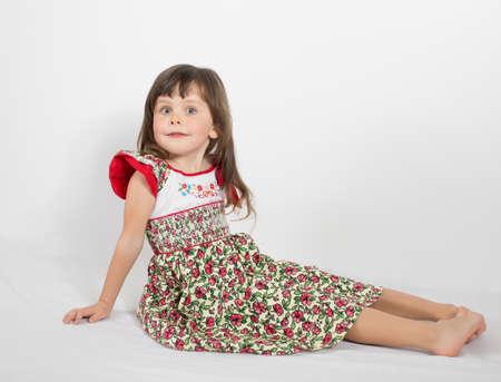 eastern european ethnicity: Portrait of preschooler girl in summer dress. Charming child posing on white background indoors. Studio shot Stock Photo