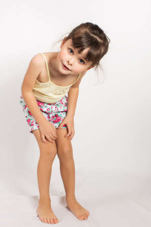 bowed head: Portrait of preschooler girl in shorts and tank top. Charming child posing on white background indoors. Studio shot
