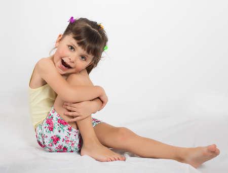 ragazze a piedi nudi: Ritratto di prescolare ragazza in pantaloncini e canottiera. Charming bambino posa su sfondo bianco chiuso. Studio shot