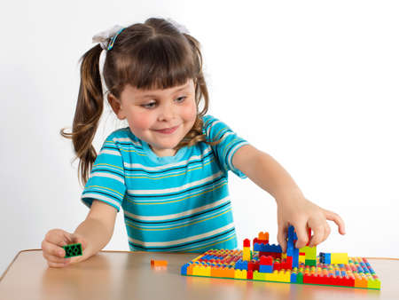 lego: Charming preschooler playing with small constructor. Little girl playing with connecting toy cubes