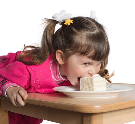 stoop: Charming preschooler in pink lays on table and eats cake. Little girl eating dessert