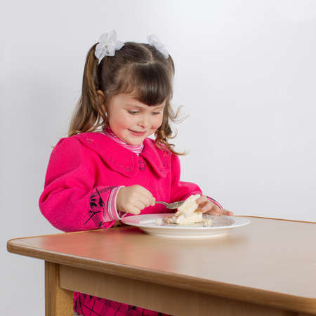 eastern european ethnicity: Charming preschooler in pink eats cake. Little girl at the table