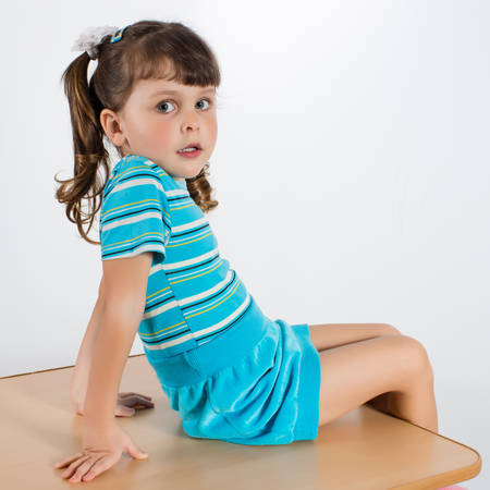Charming preschooler in blue sits on table and looks at camera. Little girl posing indoor
