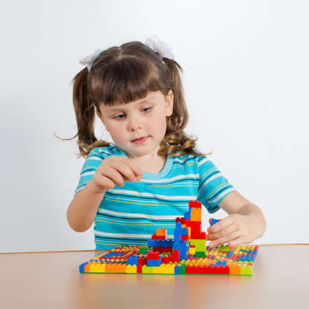 Charming preschooler playing with small constructor. Little girl playing with connecting toy cubes