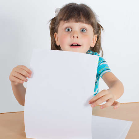russian ethnicity caucasian: Charming preschooler showing clear white sheet of paper. Little girl at the table Stock Photo