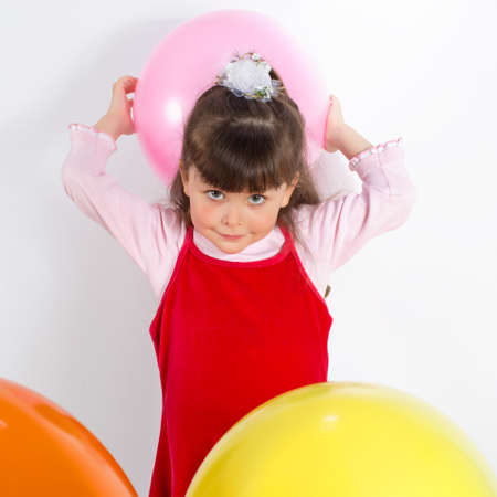 russian ethnicity caucasian: Preschooler girl with air balloons. Charming child in red dress tossing balloon. Studio shot