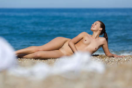 20s naked: Girl at the sea. Naked young woman tans on seashore