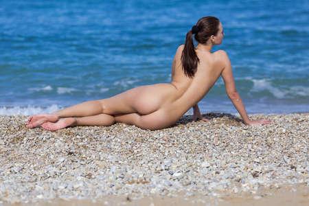Girl at the sea. Naked young woman tans on seashore