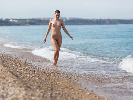 Girl at the sea. Naked young woman walking along seashore