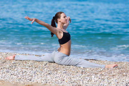non moving activity: Sportswoman doing gymnastic twine on pebble beach. Female fitness on seashore