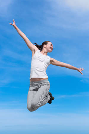 eastern european ethnicity: Hopping girl. Young woman in white blouse and sporting trousers jumps against the sky