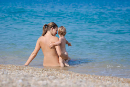 Mother with child at the sea. Naked young woman with baby rests on seashore in summer day