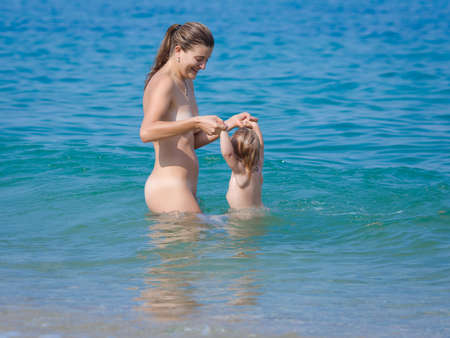 child girl nude: Mother with child at the sea. Naked young woman with baby rests on seashore in summer day