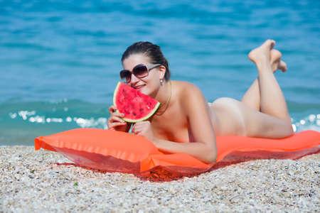 Muchacha en el mar. Mujer joven desnuda se encuentra en la piscina balsa, come sandía, mira a la cámara a través de gafas de sol Foto de archivo - 38791164
