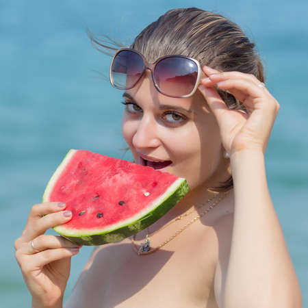 pulpy: Girl with watermelon. Young woman eats watermelon on the beach