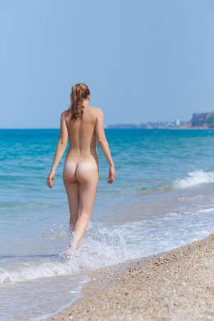 nudity woman: Girl at the sea. Naked young woman walking along seashore