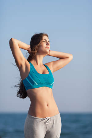 she: Athletic girl on beach. Young long-haired woman standing against of sea with hands on head. She sunbathes with eyes closed Stock Photo
