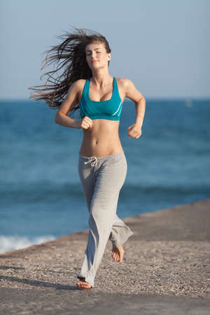 bra top: Jogging. Barefoot slim girl running on concrete quayside against sea. Wind blowing her long hair