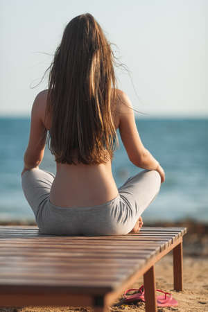 Athletic girl on beach. Back view of young long-haired woman sitting cross-legged with hands on knees Фото со стока
